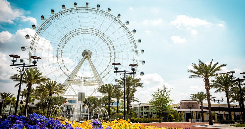 The Coca-Cola Orlando Eye with purple and yellow flowers in the forground