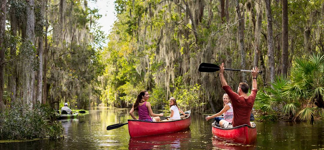 A family on a guided canoe tour through Shingle Creek in Orlando