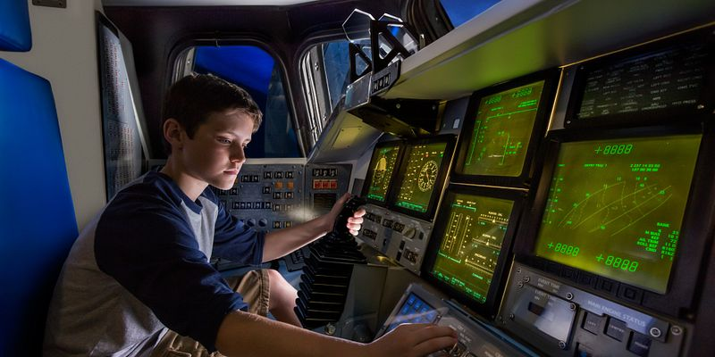 Boy in Atlantis flight deck simulator at Kennedy Space Center