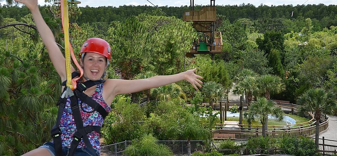 A woman riding a zipline from one tower to another at Gatorland in Orlando