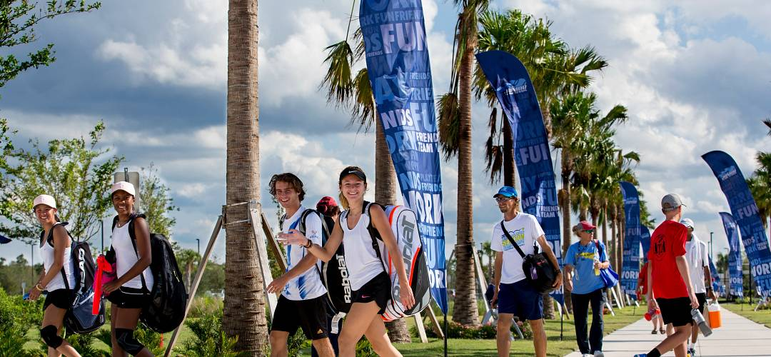 A group of tennis students walking towards the USTA Welcome Center, The Home of American Tennis® in Orlando, Florida.