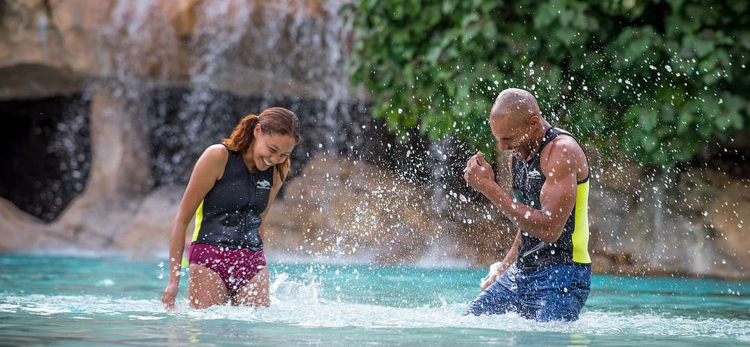 A family splashing in Serenity Bay at Discovery Cove in Orlando