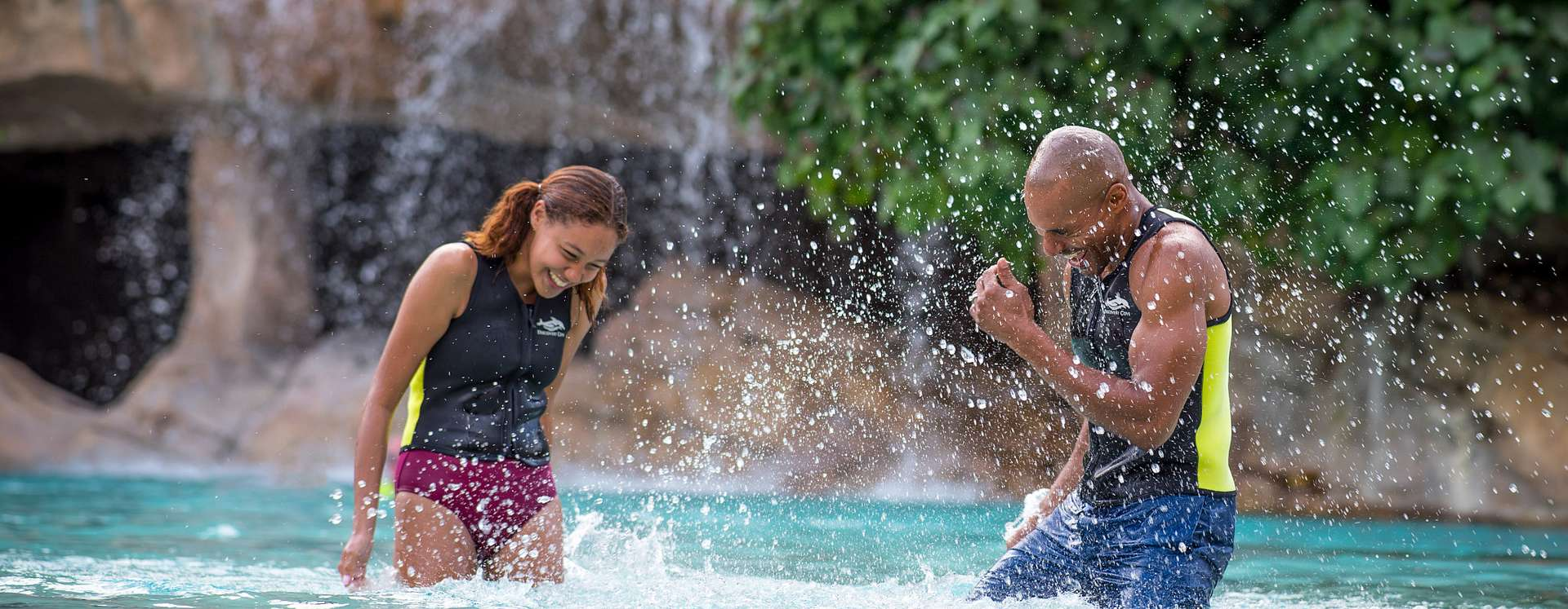 Couple having fun while splashing water at each other during their visit at SeaWorld's Discovery Cove