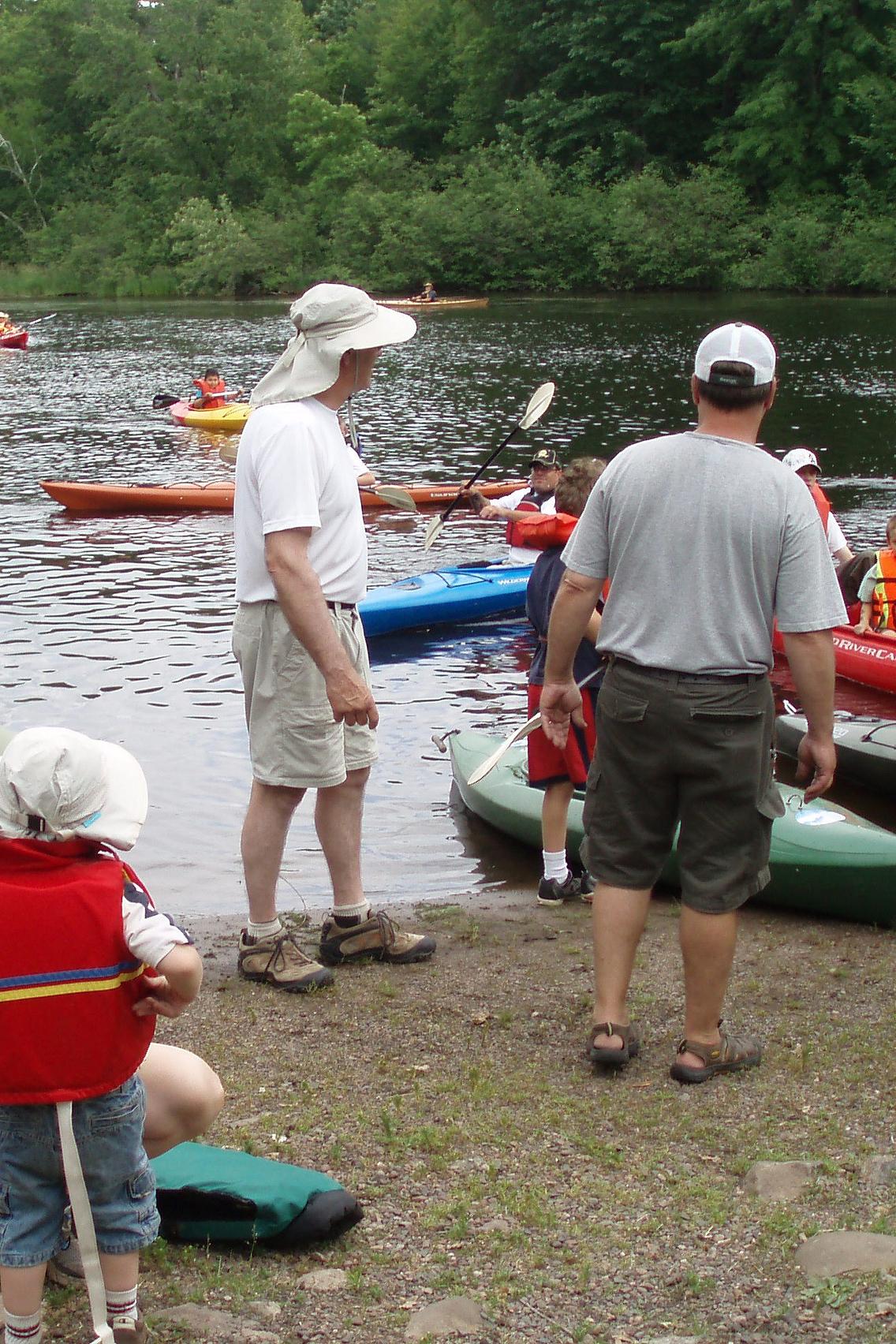 Men helping young children in kayaks on shore of lake