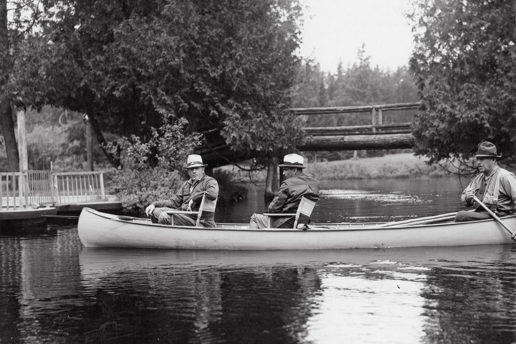 Historic photo of three men in a canoe on the Brule River