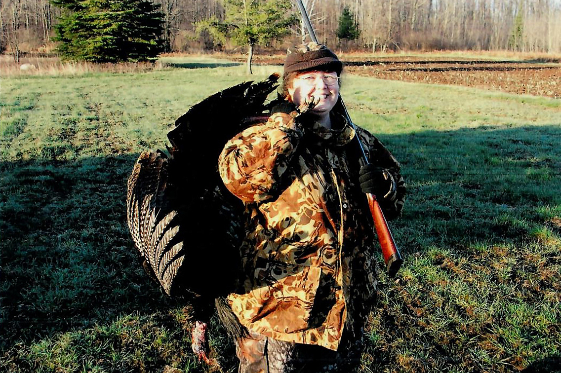 Woman in camouflage clothing in outdoor setting, holding turkey over her shoulder