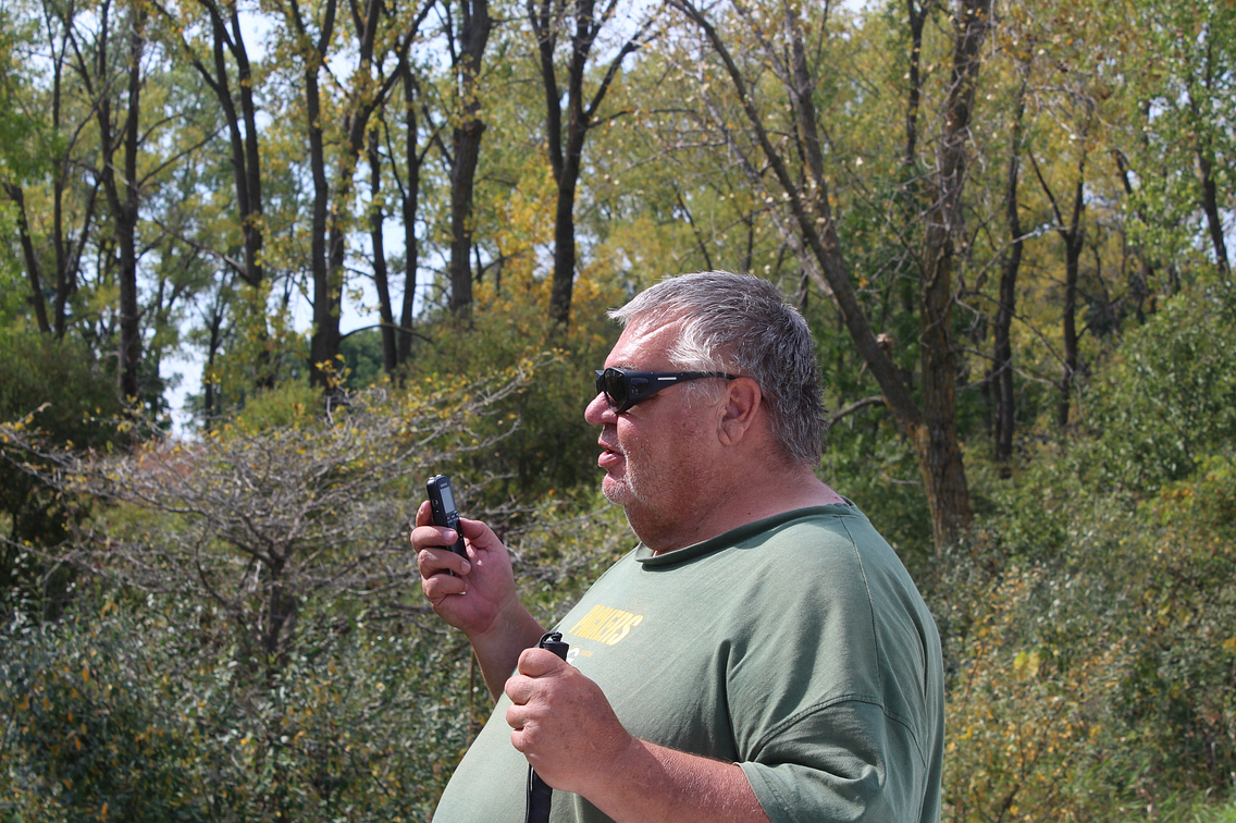 Man in forest with sunglasses on, holding a cell phone