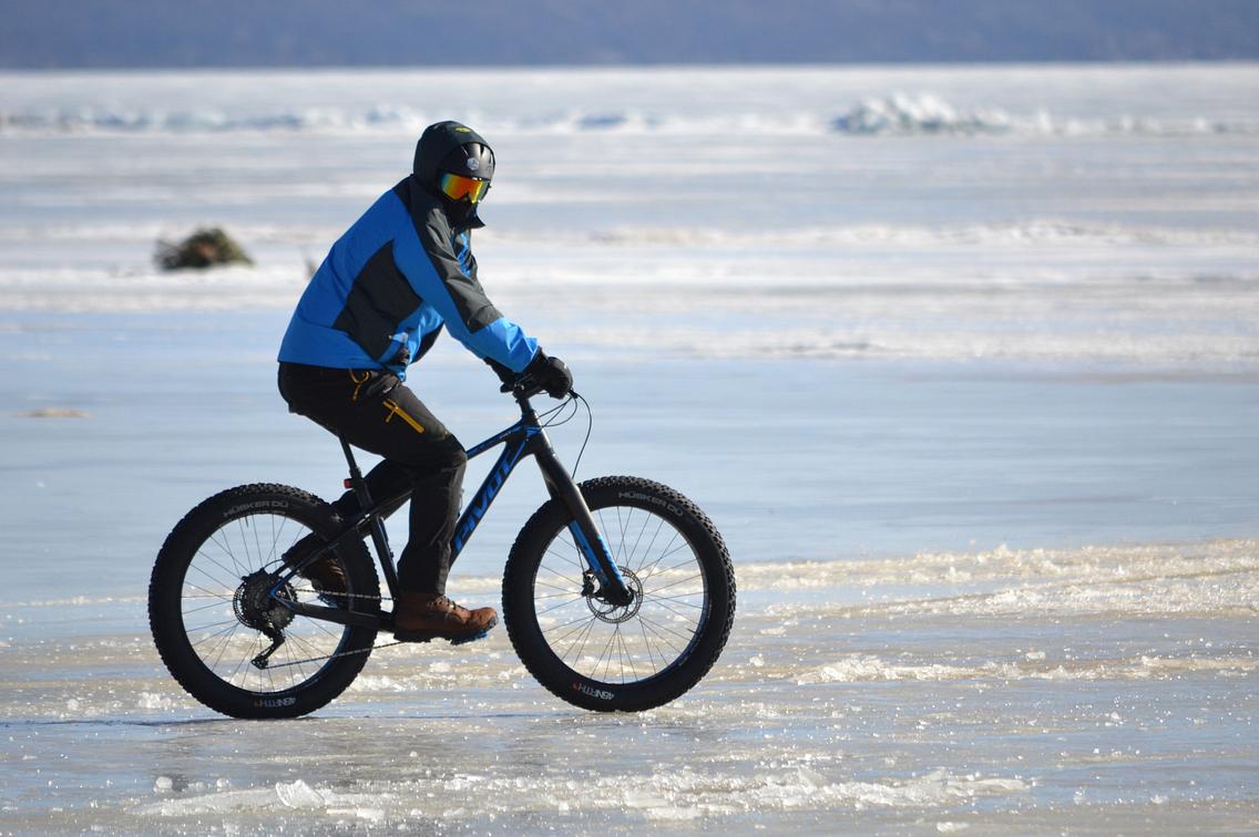 Bundled-up rider on fat-tire bike crossing frozen lake