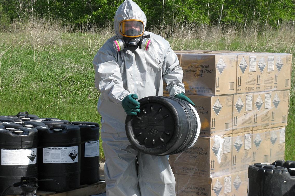 Man in haz-mat suit transferring barrels of hazardous material