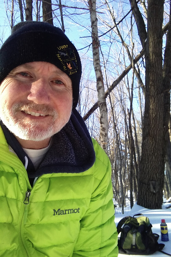 Closeup of man in neon green winter jacket in wintry, wooded setting
