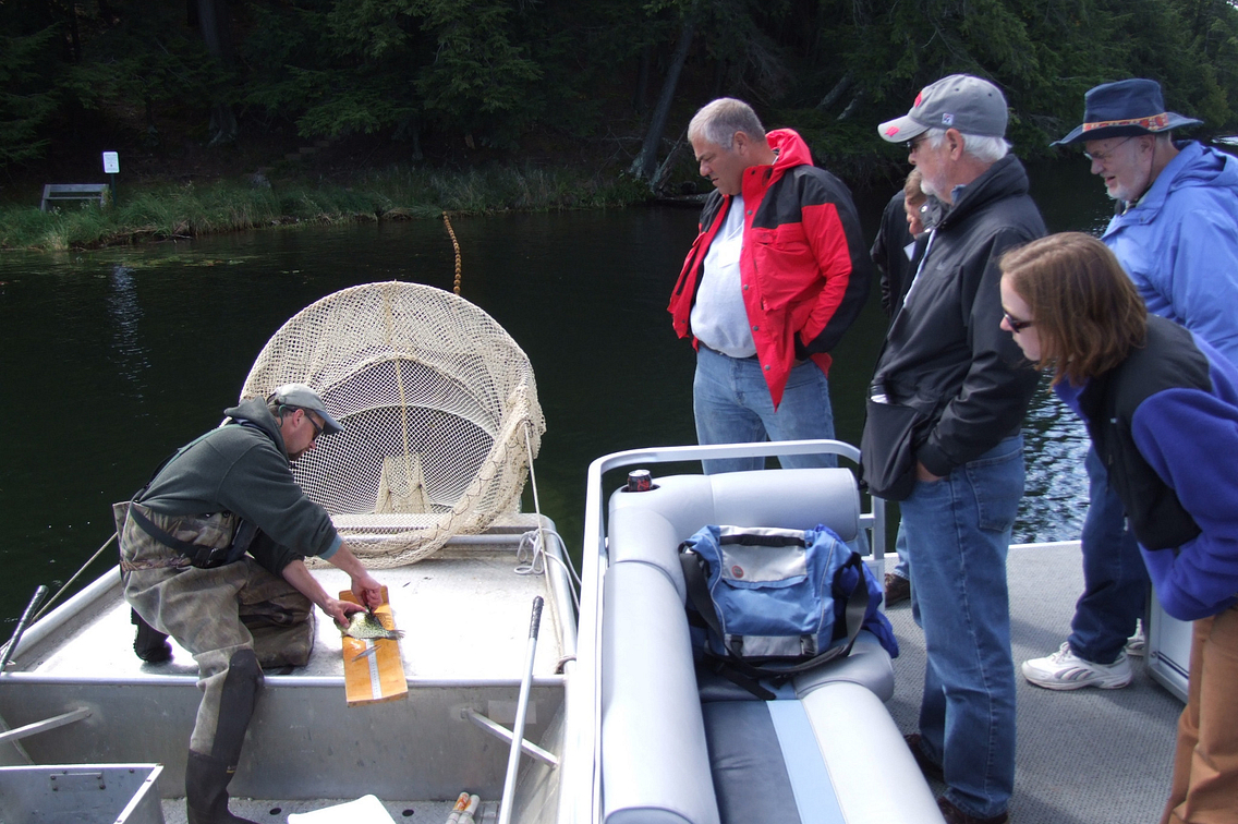 Several people looking on while a man in a boat takes a water sample