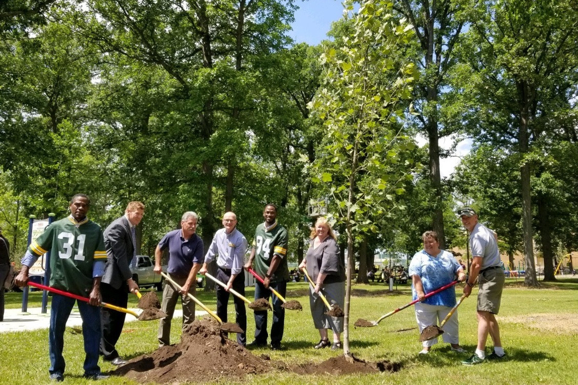 group of people holding shovels and helping plant a tree in a city park