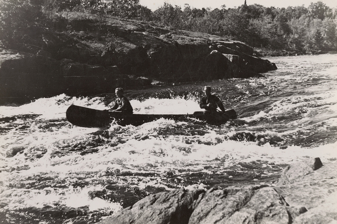 Vintage black and white photo of two men paddling canoe through river rapids