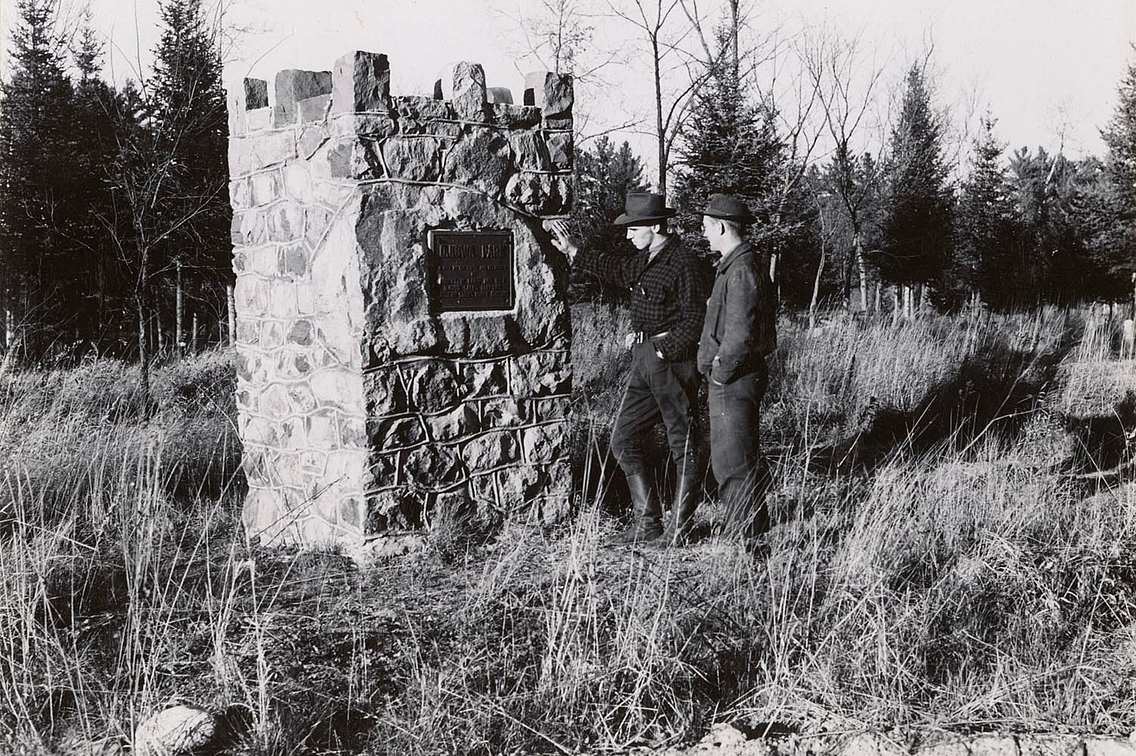 Vintage black and white photo of two men inspecting a marker at Ojibwa Roadside Park