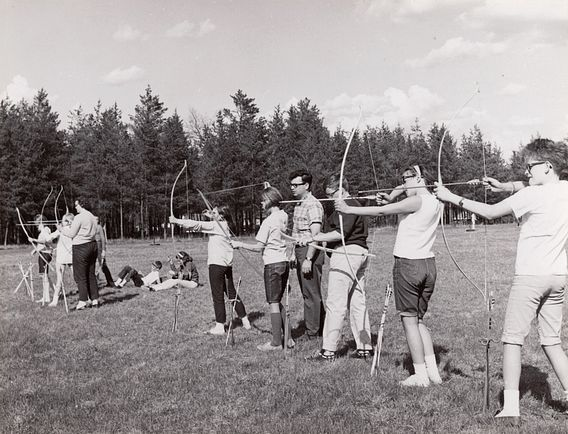 historic photo of teenagers practicing archery skills