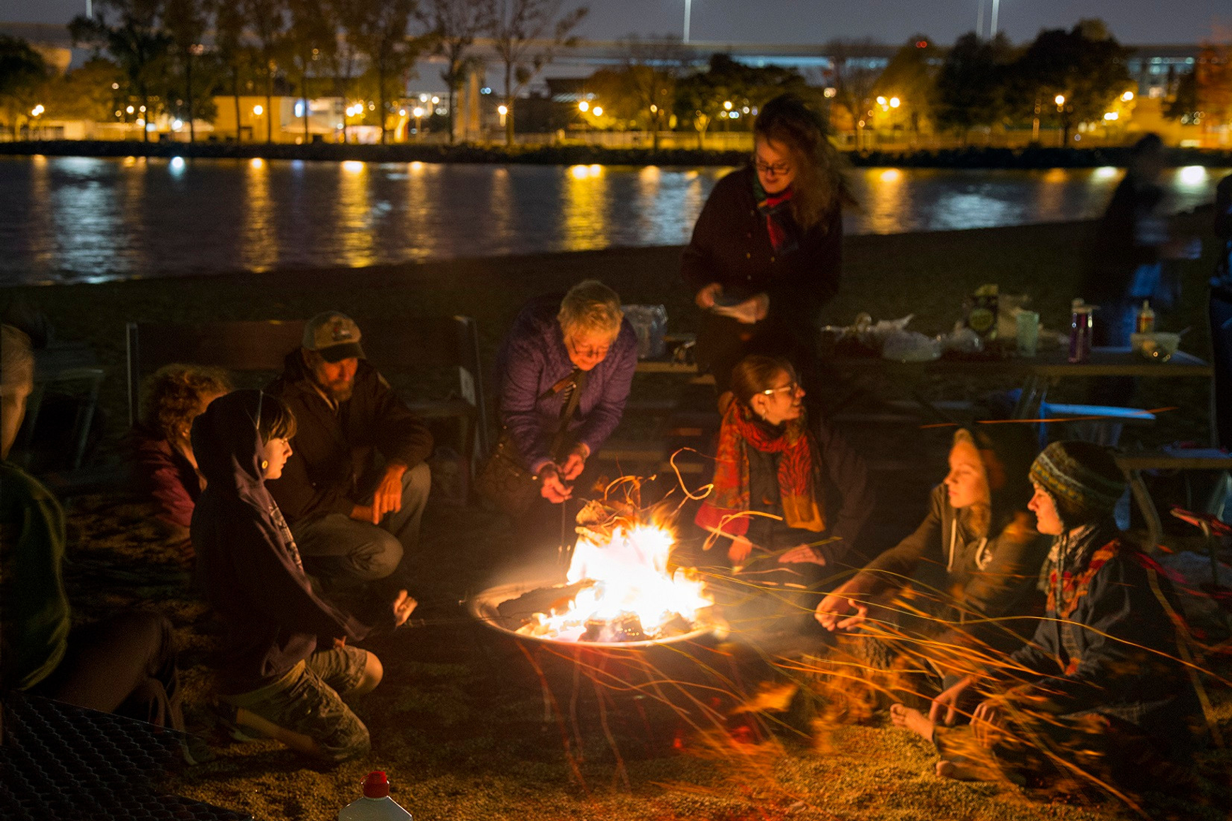People sitting near nighttime bonfire at Lakeshore State Park