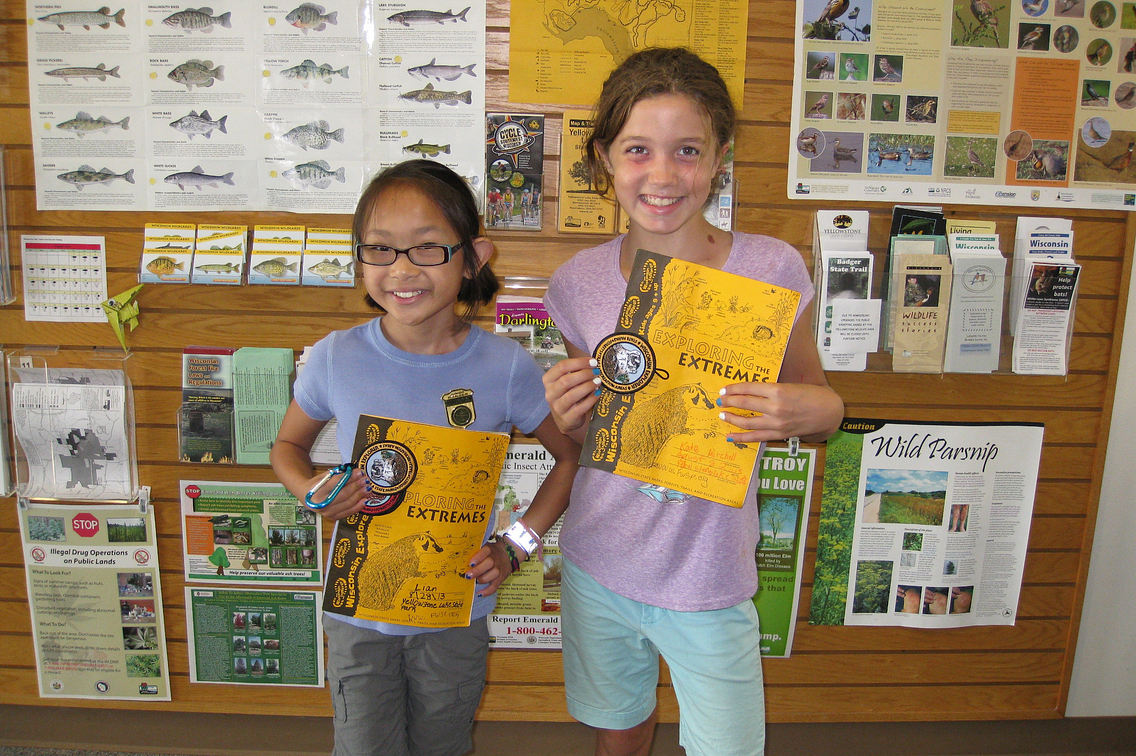 Two young girls holding Wisconsin Explorer program books