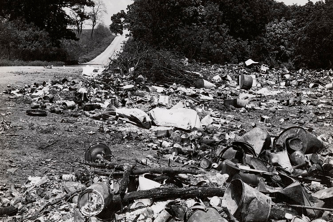 historic photo of a garbage dump near a winding road
