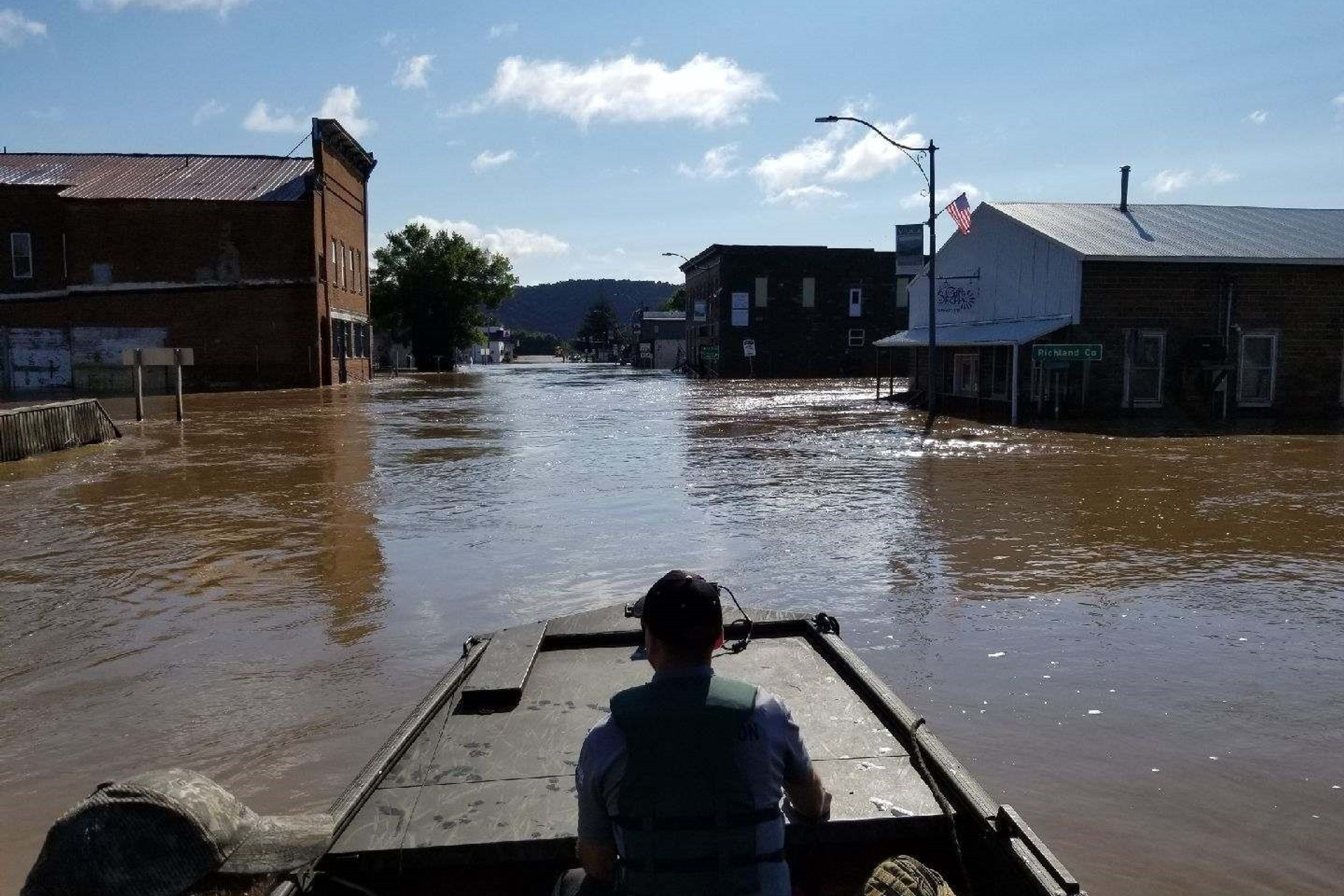 Photo of DNR warden in boat in flooded street in Viola.