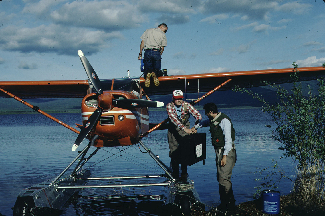 Three men working beside a seaplane in the water, one kneeling on the wings and the other two exchanging a suitcase