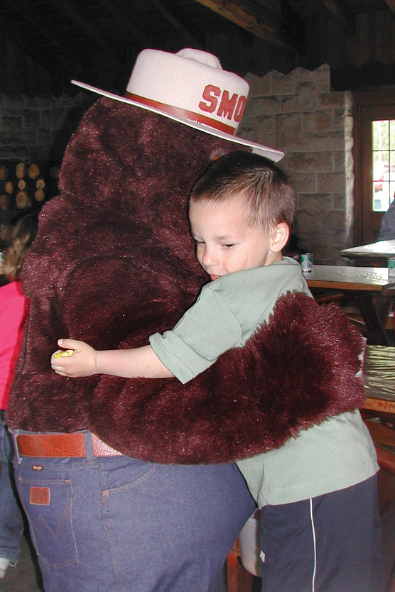 Photo of Smokey Bear hugging a young boy