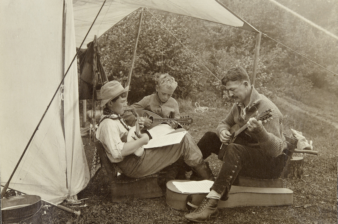 Old photo of three boys sitting under tent flap, one playing a mandolin