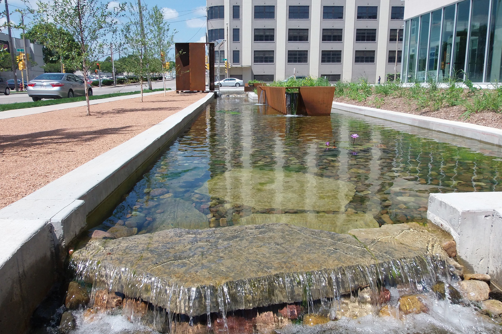 Water spilling over a rock in an urban landscaped setting