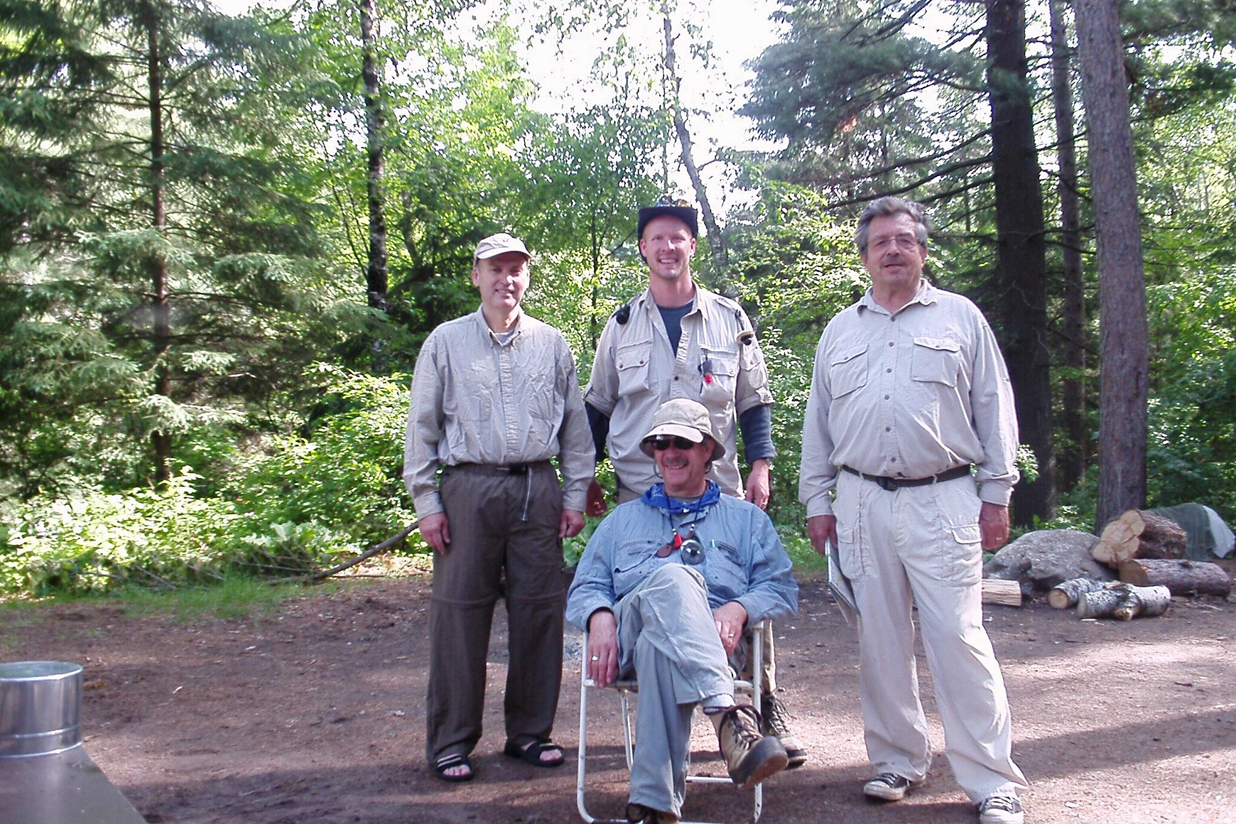 Four men in fishing clothes, three standing and one sitting