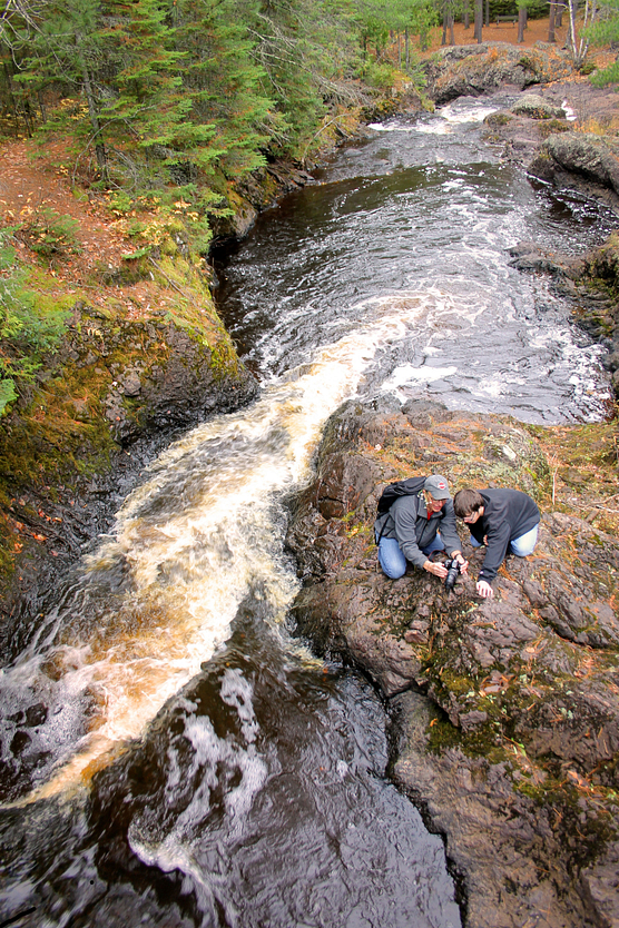 Photo of two people taking a photograph on rock overlooking fast-moving river