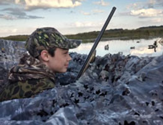 teen boy near a marsh during a morning waterfowl hunt