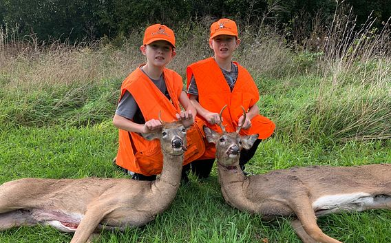 two boys in orange hunting vests with harvested deer