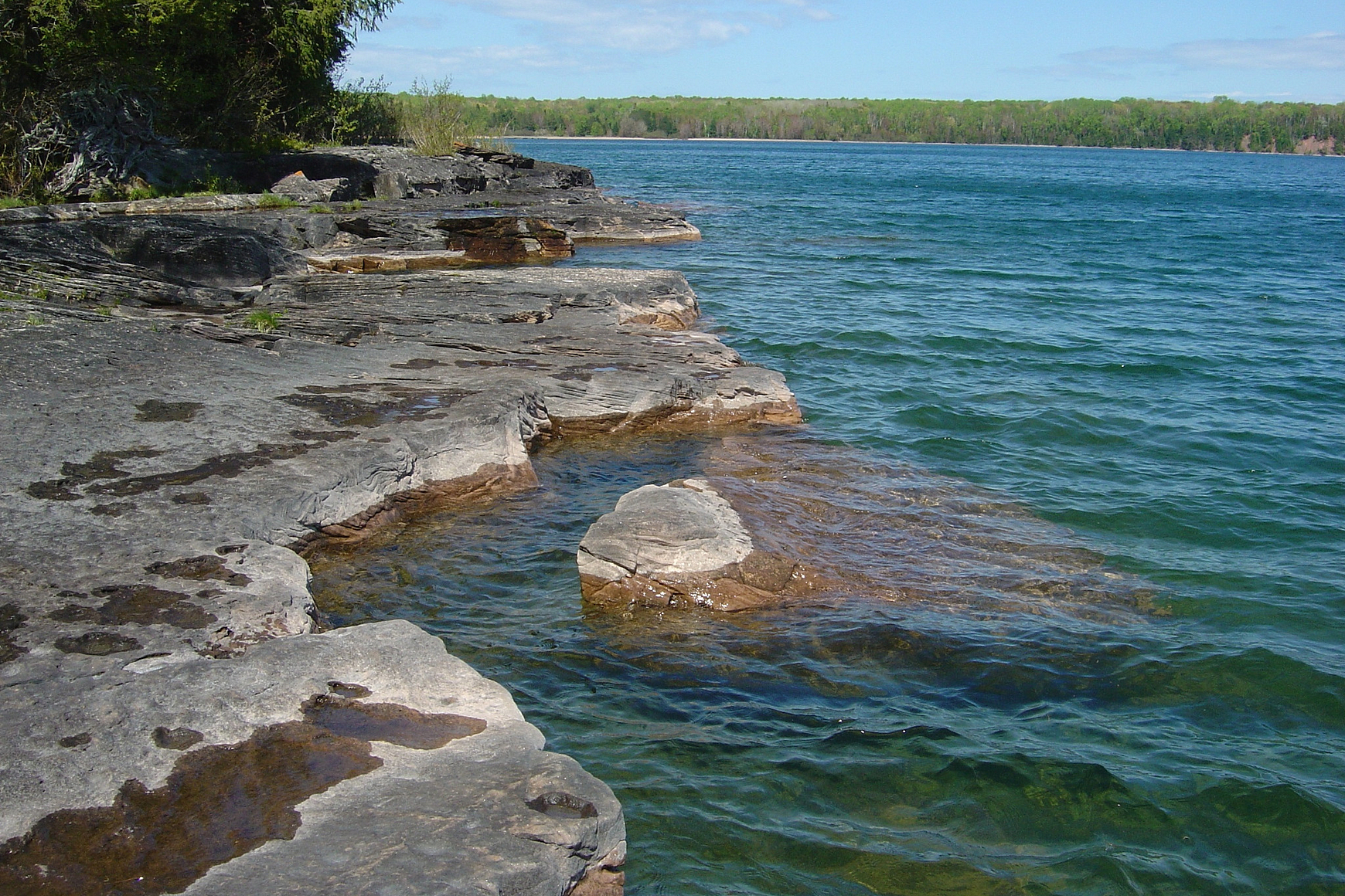 Rocky shoreline of Lake Superior on Stockton Island with blue water, trees and blue sky