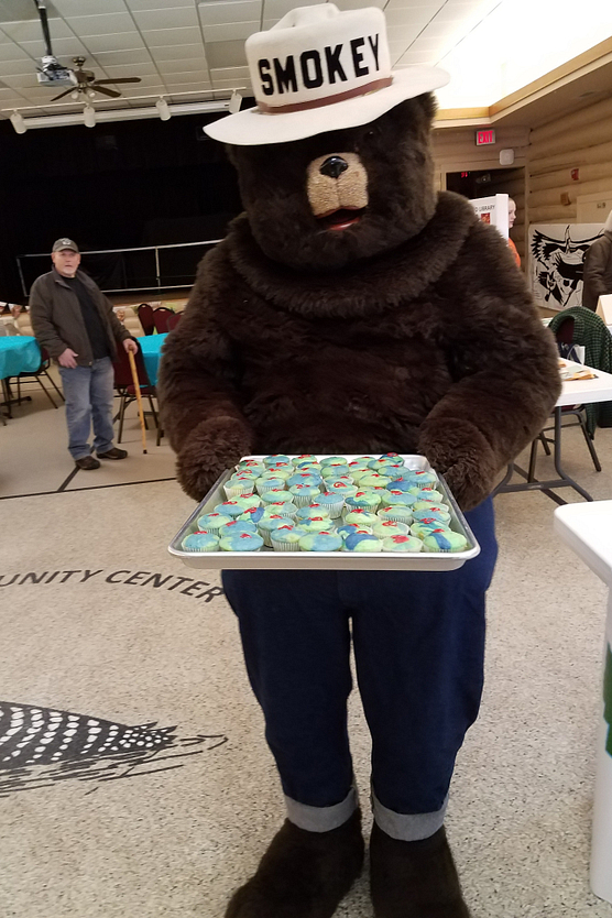 Photo of Smokey Bear holding tray of cupcakes