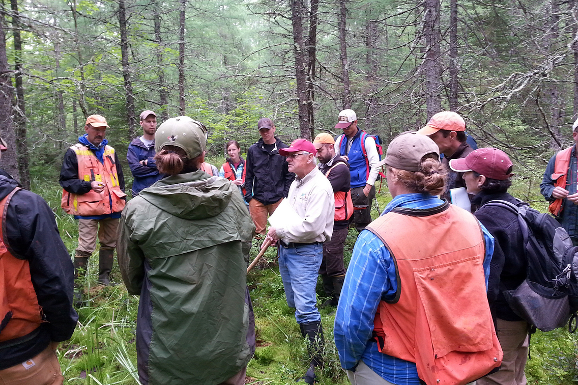 Man in red hat talking among a group of people standing in the forest