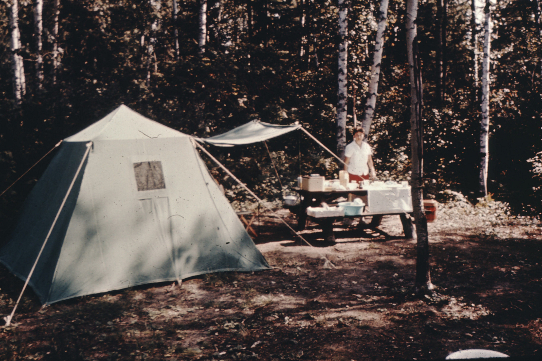 Woman standing next to picnic table at campsite
