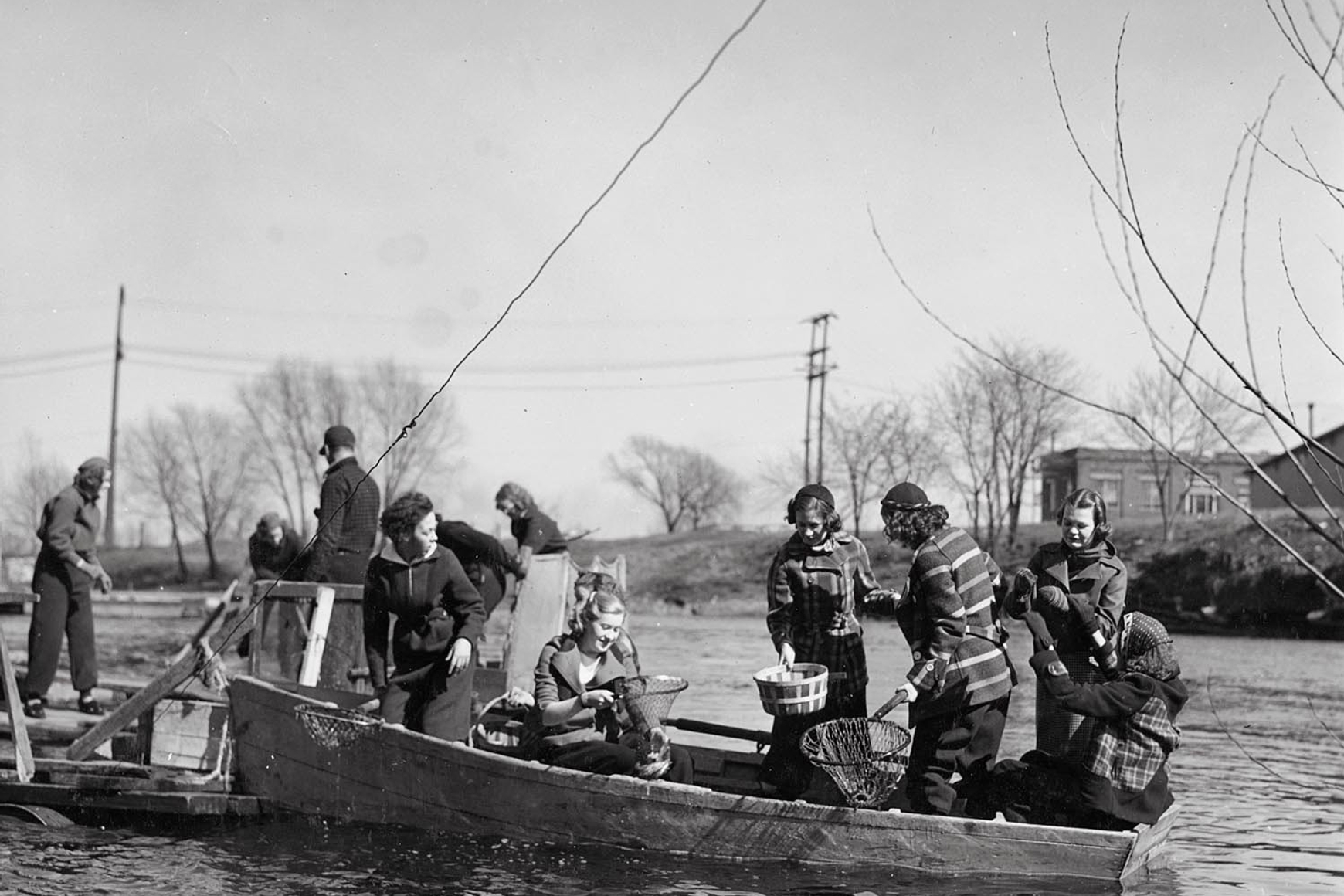 Historic photo of women dipping for smelt from boat