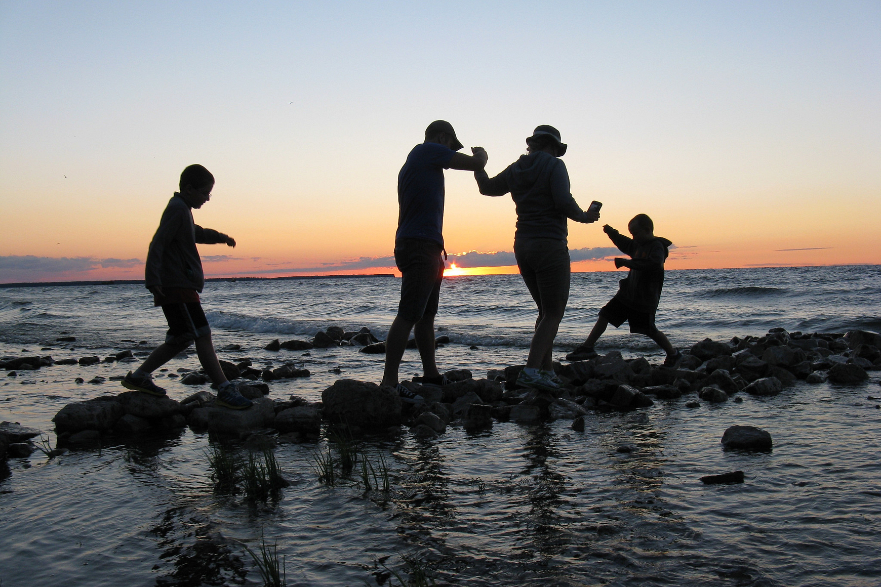 Family walking across stones near shore of Lake Michigan, silhouetted against sunset