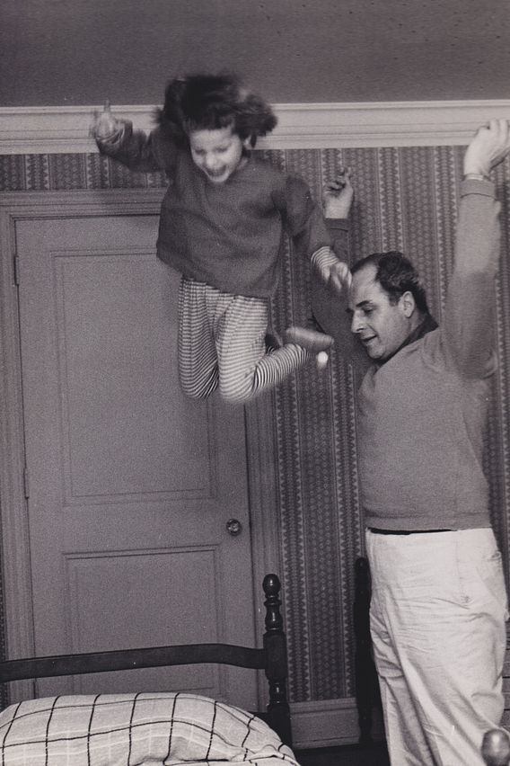 Gov. Gaylord Nelson tosses young daughter Tia into the air near a bed