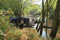 people examine boats for invasive species near marshy waterway