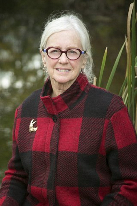 Woman with white hair, glasses and red plaid jacket
