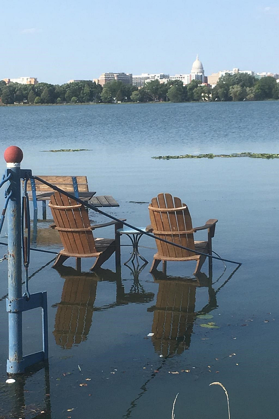 Photo of lawn chairs in flooded yard on shore of Lake Monona with capitol in background