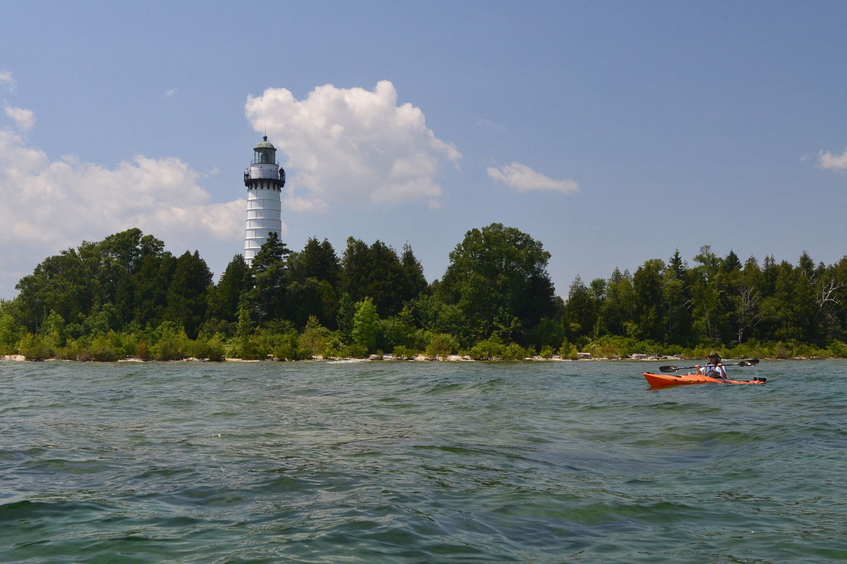 Photo of tall white lighthouse on island in Lake Michigan with kayakers paddling in water nearby