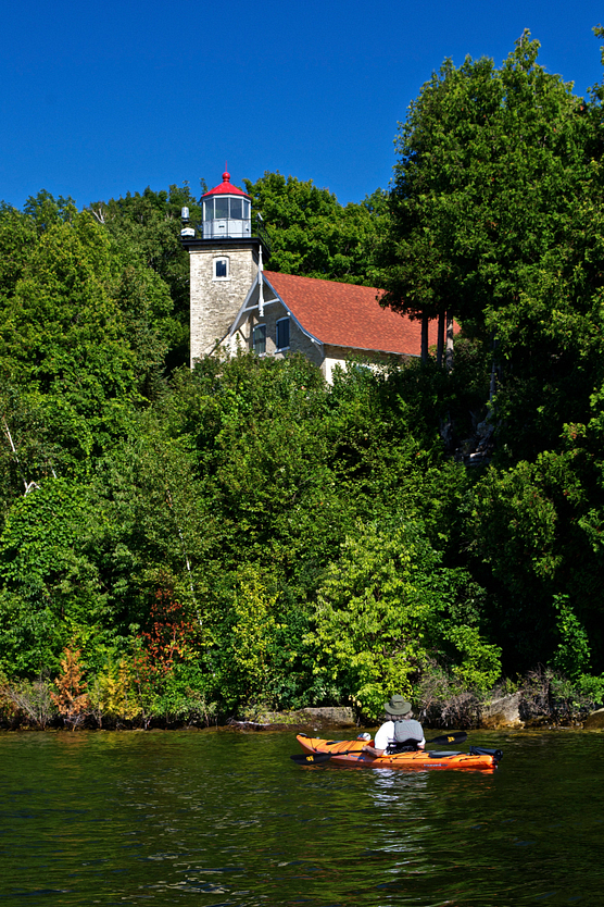 Man in kayak looking up at the Eagle Bluff Lighthouse