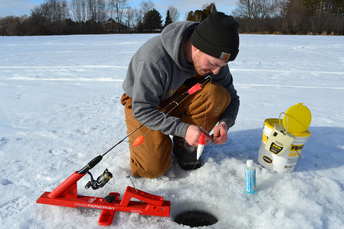 Angler fixing his line while ice fishing