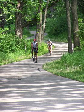 two bicyclists on winding paved trail