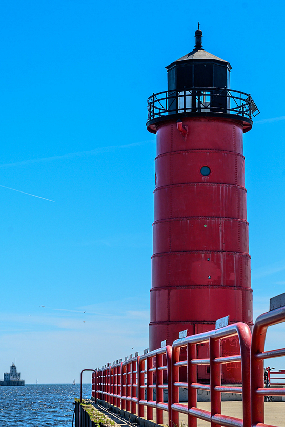 Red lighthouse against clear blue sky with sailboat and second lighthouse in Lake Michigan in the distance