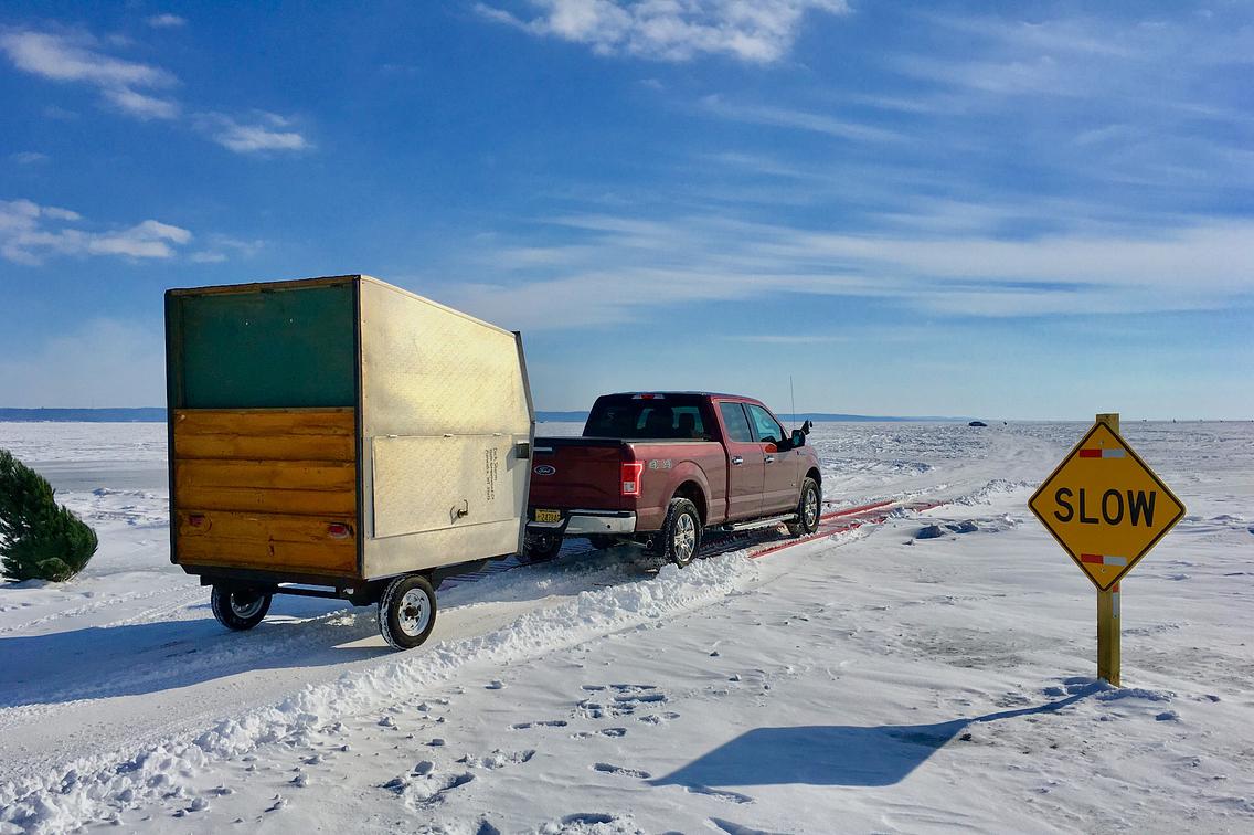 Truck pulling ice shanty across frozen lake