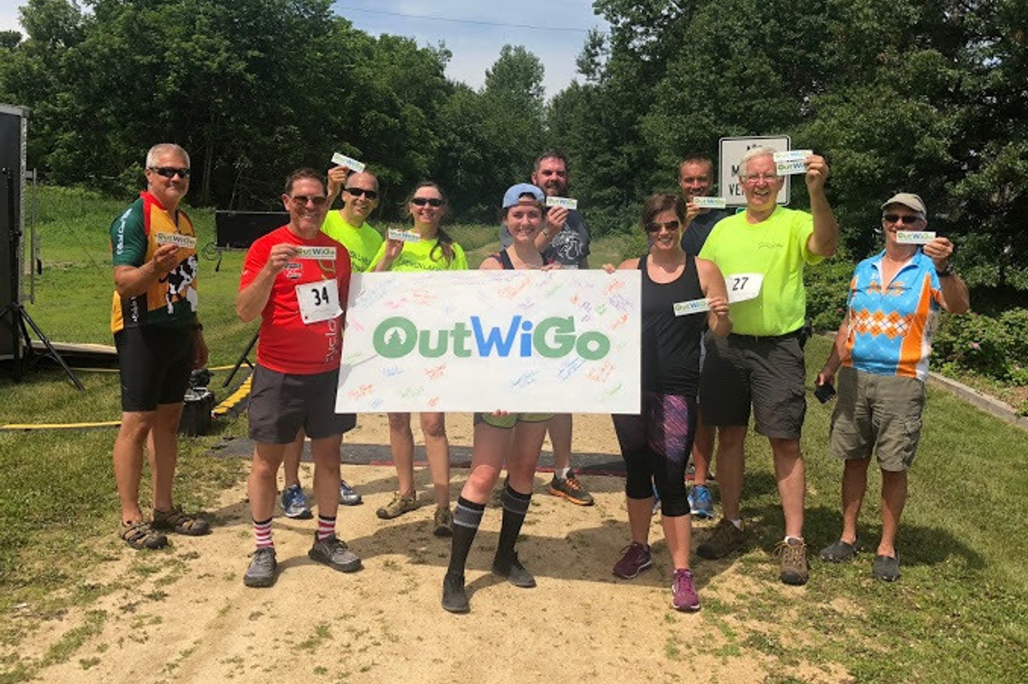 Group of people in outdoor gear with OutWiGo sign