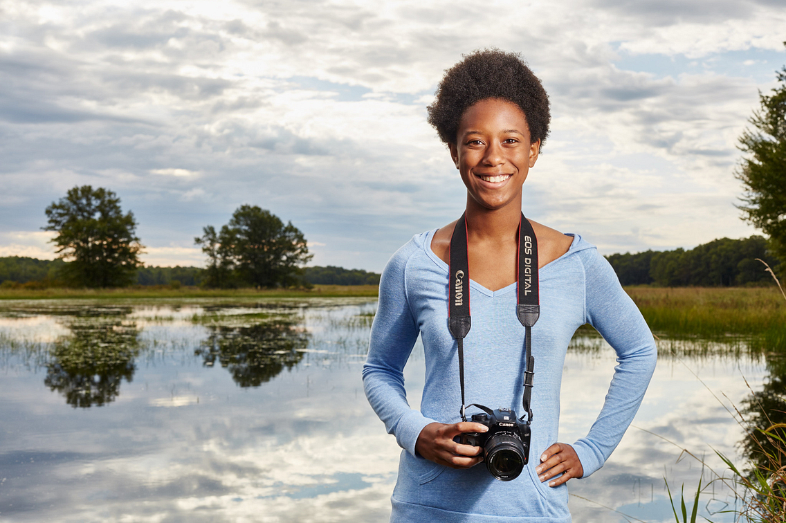 Photo of a smiling young woman with a camera around her neck, standing in the out-of-doors