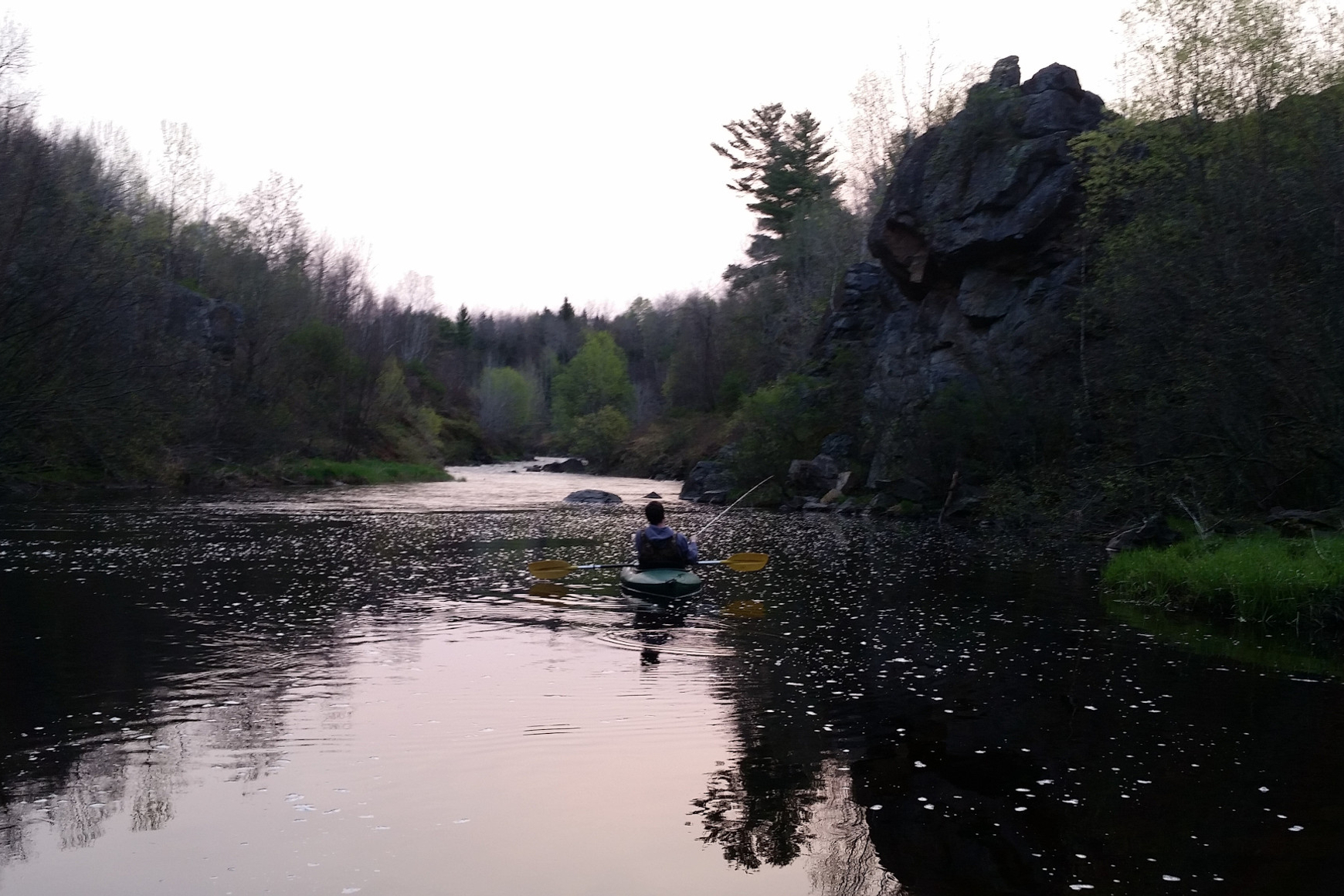 Photo of a kayaker fishing in a serene river setting